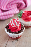 Red rose cupcakes on wooden table Stock Photos