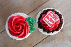 Red rose cupcakes on wooden table Royalty Free Stock Image