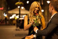 Red rose on a date. An elegant men giving his date a red rose Royalty Free Stock Photo