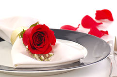 Red rose on a dniner plate. Red rose placed on a dinner plate with rose petals in a romantic setting Royalty Free Stock Photo