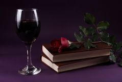 Red rose flower on books and wine glass on purple dark background. Low key. Halloween holiday concept Stock Photos