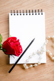 Red rose flower and pencil on blank diary. Royalty Free Stock Photos