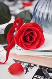Red rose flower with a stack of postcard, retro photos and vintage book Stock Photos