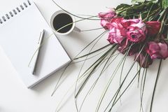 Red Rose Flowers Bouquet on White Surface Beside Spring Book With Click Pen and Cup of Cofffee royalty free stock photography
