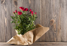 Red rose flowers in paper-bag on a wooden background Stock Photo