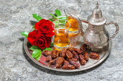 Red rose flowers with tea and dates fruits. Islamic holidays. Ra stock photography