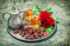 Red rose flowers with tea and dates fruits. Ramadan. Vintage sty stock image