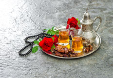 Red rose flowers tea dates Islamic holidays decoration. Red rose flowers with tea and dates. Islamic holidays decoration. Ramadan kareem Royalty Free Stock Photos