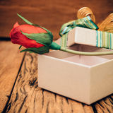 Red rose in gift box on old wood background. Royalty Free Stock Photos