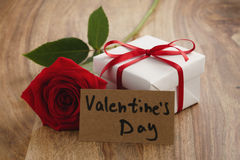 Red rose with gift box and valentines day card on wooden table. Shallow focus Stock Photography