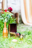 Red Rose in gilded bottle. Red Rose in a gilded bottle at the open boxes on the green grass Stock Photo
