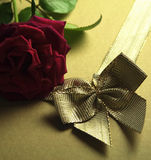 Red rose and golden ribbon Stock Photos
