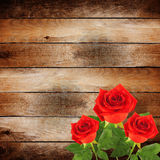 Red rose with green leaves on the wooden background Royalty Free Stock Photo