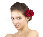 Red rose in hair of young cute woman. On white background royalty free stock photography