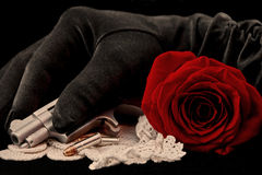 Red Rose with handgun and bullets with hand in black glove Royalty Free Stock Photo