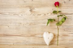 A red rose with a heart. In front of a wood background Royalty Free Stock Photos