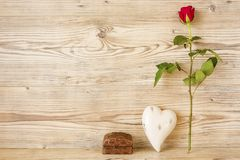 Red rose with heart and gift. In front of a wood background Royalty Free Stock Images