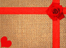 Red rose and heart on linen texture background with red ribbon Stock Photos