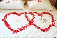 Red rose hearts on white bed. Stock Images