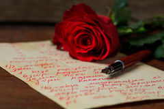 Red rose and an ink pen on a letter. Red rose and an ink pen on a handwritten letter Stock Photos