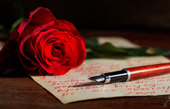 Red rose and an ink pen on a letter. Red rose and an ink pen on a handwritten letter Royalty Free Stock Images