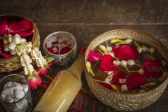 Red rose, Jasmine and popped rice on the calm water surface placed on the wood table Ready for pour water on the hands of revered stock photo
