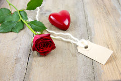 Red rose, label tag and plastic heart Royalty Free Stock Photo