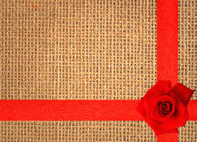 Red rose on linen texture background with red ribbon Royalty Free Stock Photography