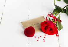 Red rose, love message, casket with a ring Stock Photography