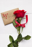 Red rose, love message on a white wooden background Stock Photos