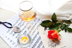 Red rose with music. Beautiful red rose with music notes, glass and burning candle Royalty Free Stock Photography