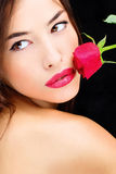 Red rose near lips and naked shoulder Royalty Free Stock Images