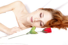 Red rose near pretty red-haired sleeping woman Royalty Free Stock Photo