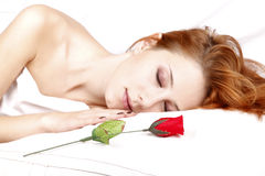 Red Rose Near Pretty Red-haired Sleeping Woman Stock Image