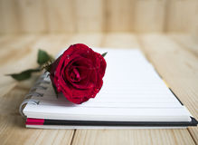 Red rose and notebook page 1 Stock Photo