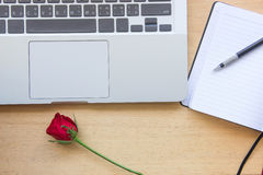 Red rose, notebook, pencil and laptop on wooden table for love c Royalty Free Stock Photography