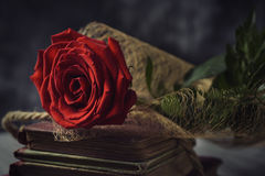 Red rose and old books. A red rose on a pile of old books, on a rustic surface, for Sant Jordi, the Catalan name for Saint Georges Day, when it is tradition to Stock Image