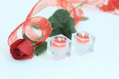 Red rose and a pair of candles on a white background.photo with. Copy space Stock Photos