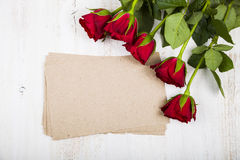 Red rose and paper for congratulations on a wooden background. Stock Photo