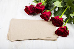 Red rose and paper for congratulations on a wooden background. Stock Images