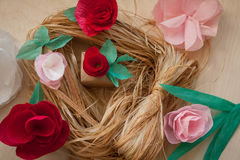 Red and rose paper flowers. Gift and Red, rose paper flowers on the wooden background and bast. Cut from paper. Place for your text Royalty Free Stock Photo