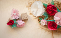 Red and rose paper flowers. Gift, Red and rose paper flowers on the wooden background and bast. Cut from paper. Place for your text Royalty Free Stock Images