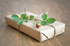 Red rose and parcel  wrapped in brown paper Stock Images