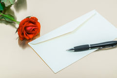 Red rose with a pen and a blank letters Stock Photo