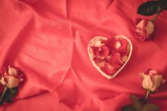 Red rose petal in heart shape. With red background stock images