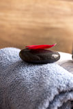 Red rose petal lying on black zen stone. Closeup of red rose petal lying on black zen stone on top of blue rolled towel Stock Photo