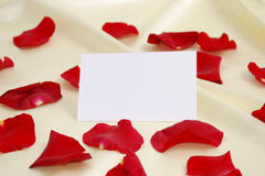 Red rose petals. And blank invitation card on golden satin royalty free stock images