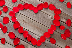 Red rose petals heart over wooden background Royalty Free Stock Image