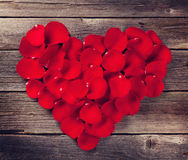 Red rose petals heart. Over wooden table. Top view. Retro toned stock images