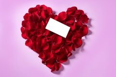 Red rose petals in heart shape Stock Image